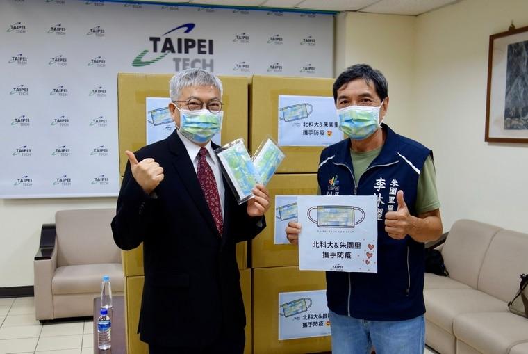 北科大校長王錫福(圖左)將口罩圈贈給朱園里里長李林耀(圖右),一起攜手防疫。北科大提供